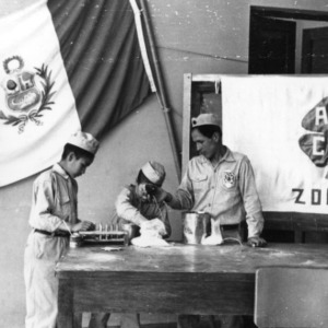 Three 4-H club members in Peru making chalk as a demonstration