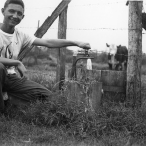 4-H club member filling a water container next to a fence