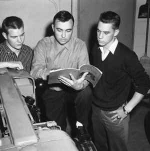 4-H club members consulting a manual while at a 4-H tractor program