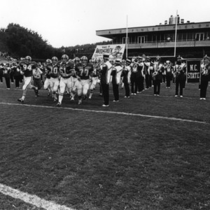 Marching band greets football players on the field
