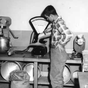 4-H club boy placing scoop of grain on a scale