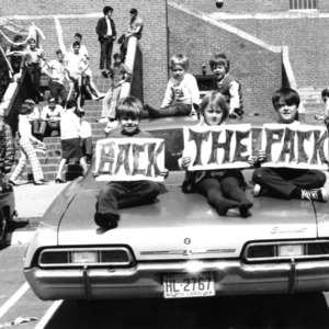 N. C. State fans on a car in front of Reynolds Coliseum