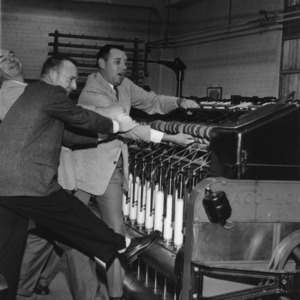 Several men posing with a textile machine