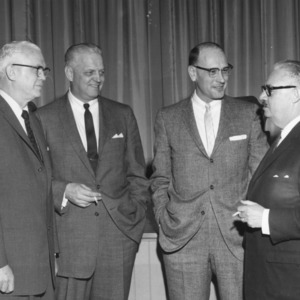 Malcolm E. Campbell, Dean, School of Textiles (far right) talking with three unknown men
