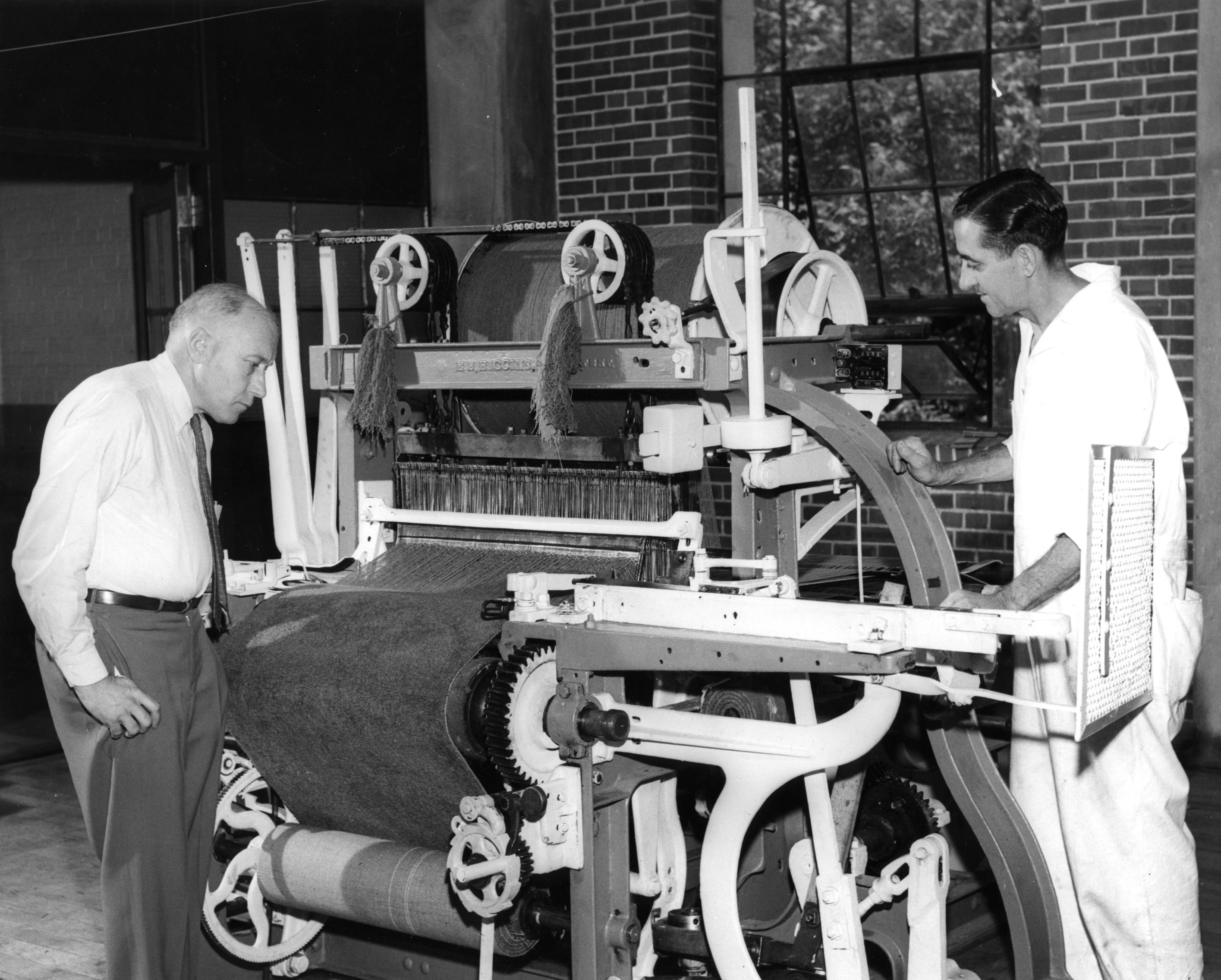 Professor Whittier (left) inspects a carpet loom by Bigelow Sanford, N.C.