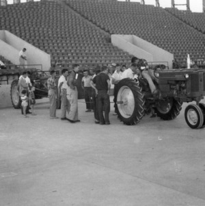 4-H club members examining a tractor at a tractor contest, September 23, 1953
