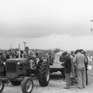 4-H club member drives a tractor while other look on at the 4-H tractor program