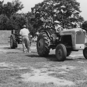 4-H club boy driving tractor around course, 4-H tractor program