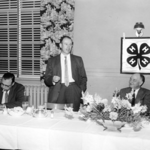4-H club leader speaking at a meeting at a 4-H tractor program, to his right sits L. R. Harrill, North Carolina State 4-H Club leader
