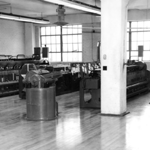 Interior view of a textile machine lab, probably in Tompkins Hall