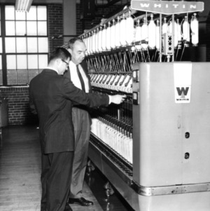 Professor E. B. Grover and L. T. Lassiter examining a Whitin machine
