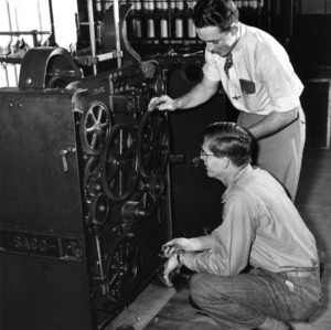 Two men examining a Saco-Lowell machine, probably in Tompkins Hall