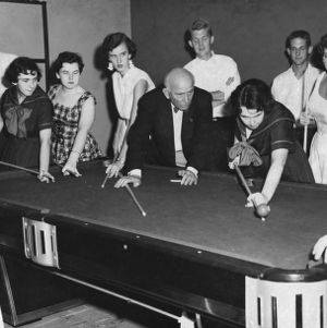 Girls learning to play pool