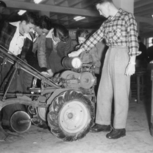 4-H club boys examining engine on a piece of farm machinery