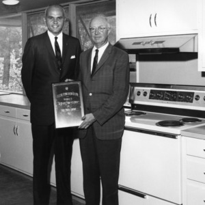Douglas W. Booth and other standing in an electric demonstration kitchen donated by Duke Power Company at the Betsy-Jeff Penn 4-H Educational Center