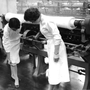 Two women working in a textile factory with a knitting machine
