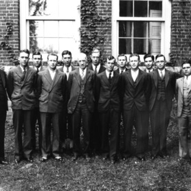 Group portrait in front of Tompkins Hall. Dean Thomas Nelson is sixth from left.