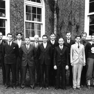 Group portrait of students and faculty in front of Tompkins Hall