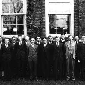 Group portrait of male students and faculty in front of Tompkins Hall. Dean Thomas Nelson is fifth from left.