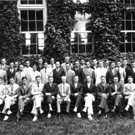 Group portrait of textiles faculty and students in front of Tompkins Hall. Dean Thomas Nelson in first row, sixth from left
