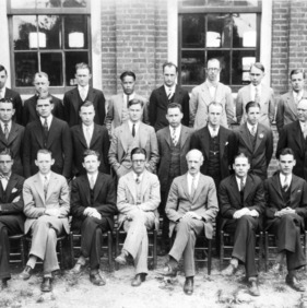 Group portrait of textile faculty and students in front of Tompkins Hall. Dean Thomas Nelson sits in front row, thrid from right. Professor Hart stands in second row, far right.