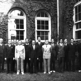 Group portrait of textile students and faculty in front of Tompkins Hall. Dean Thomas Nelson stands on left.