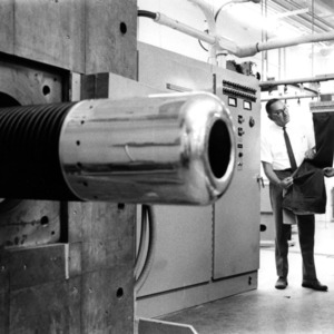 Professor Henry A. Rutherford and Dr. William Walsh, head of the radiation lab, talk next to an electron accelerator