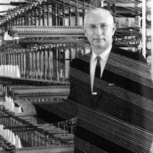 Dean David Chaney posing with a textile machine