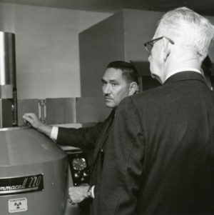 Dr. Henry A. Rutherford and other looking over Gammacell 220 machine, the source of Cobalt-60, used for fiber modification by atomic radiation