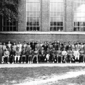 Graduating class at the Textile School of North Carolina State College in front of Tompkins Hall. Dean Thomas Nelson in front row, seventh from left.