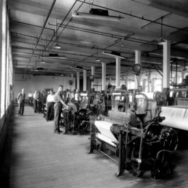 Dean Thomas Nelson standing on left in textile machine room in Tompkins Hall