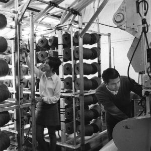 School of Textiles student (left) pieces end in the creel on the carpet tufting machine. Student on the right threads the tufting machine.