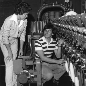 Two students discussing textile machinery