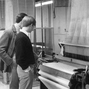 Students examining jacquard weaving machine