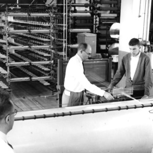 Student receiving help from a professor with a textile machine