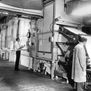 Two men examining a textile machine