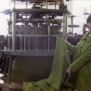Woman posing with the machine she used to make the coat she is wearing