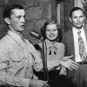 4-H club member James Willeus singing at a microphone while two other unidentified people look on