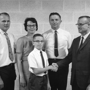 4-H club member shaking hands with four adults