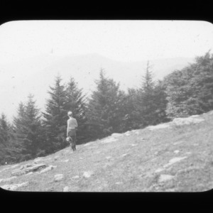 A man standing on a downhill inspecting the view