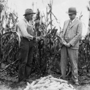 Mr. Clifford Mabry taking some seed corn suggestions from Mr. J. W. Goodman, district agent, 1930