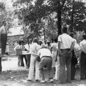 Dr. Luther Shaw, extension plant pathologist, delivers a noon-time talk to a group of Johnston County farmers who went on the farm tour. Dinner was served at the home of Mr. Joel A. Johnson, August 10, 1938