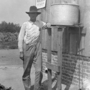 J. T. Morgan standing next to his new oil-burning tobacco curing furnace, near Zebulon, North Carolina, September 14, 1927