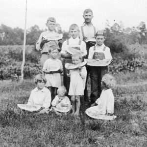 Mr. Ernest Sledge and his children eating watermelon, August 29, 1927