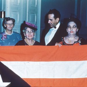 Governor William Kerr Scott and Mrs. Scott behind women holding a Puerto Rican flag