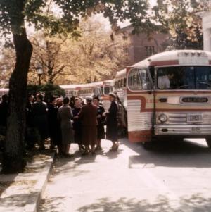 Women gathered next to tour buses