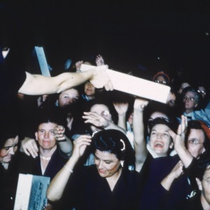 Women in a crowd of conference participants reaching for object