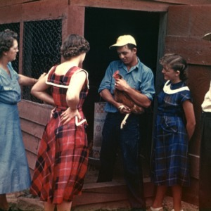 Family gathers at their chicken coop
