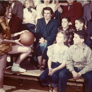 Female basketball player talks with her family on the sidelines