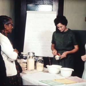 Demonstrating the making of cornmeal mix